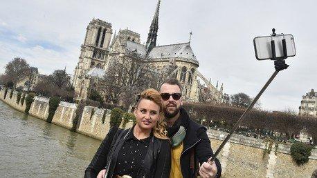 Des touristes prenant une photo près de Notre-Dame