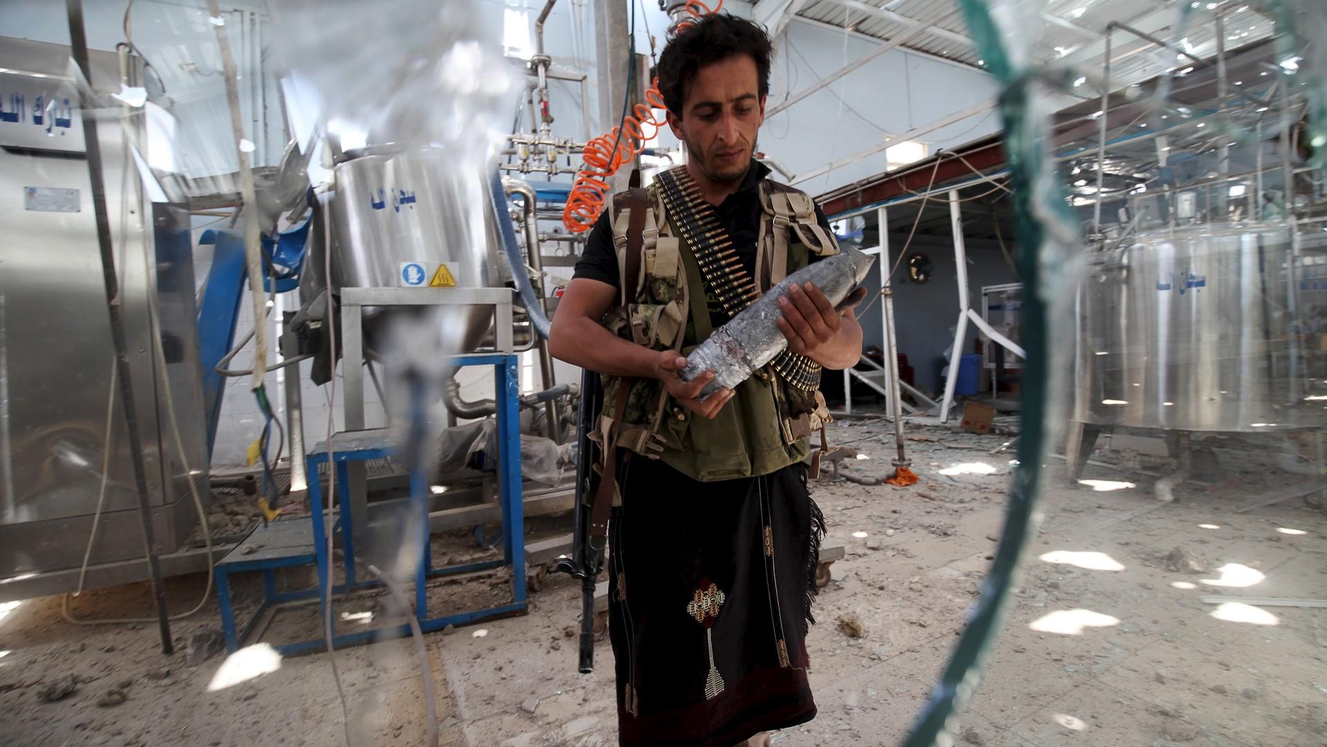 Un gardien regarde un obus d'artillerie dans une usine de Sanaa