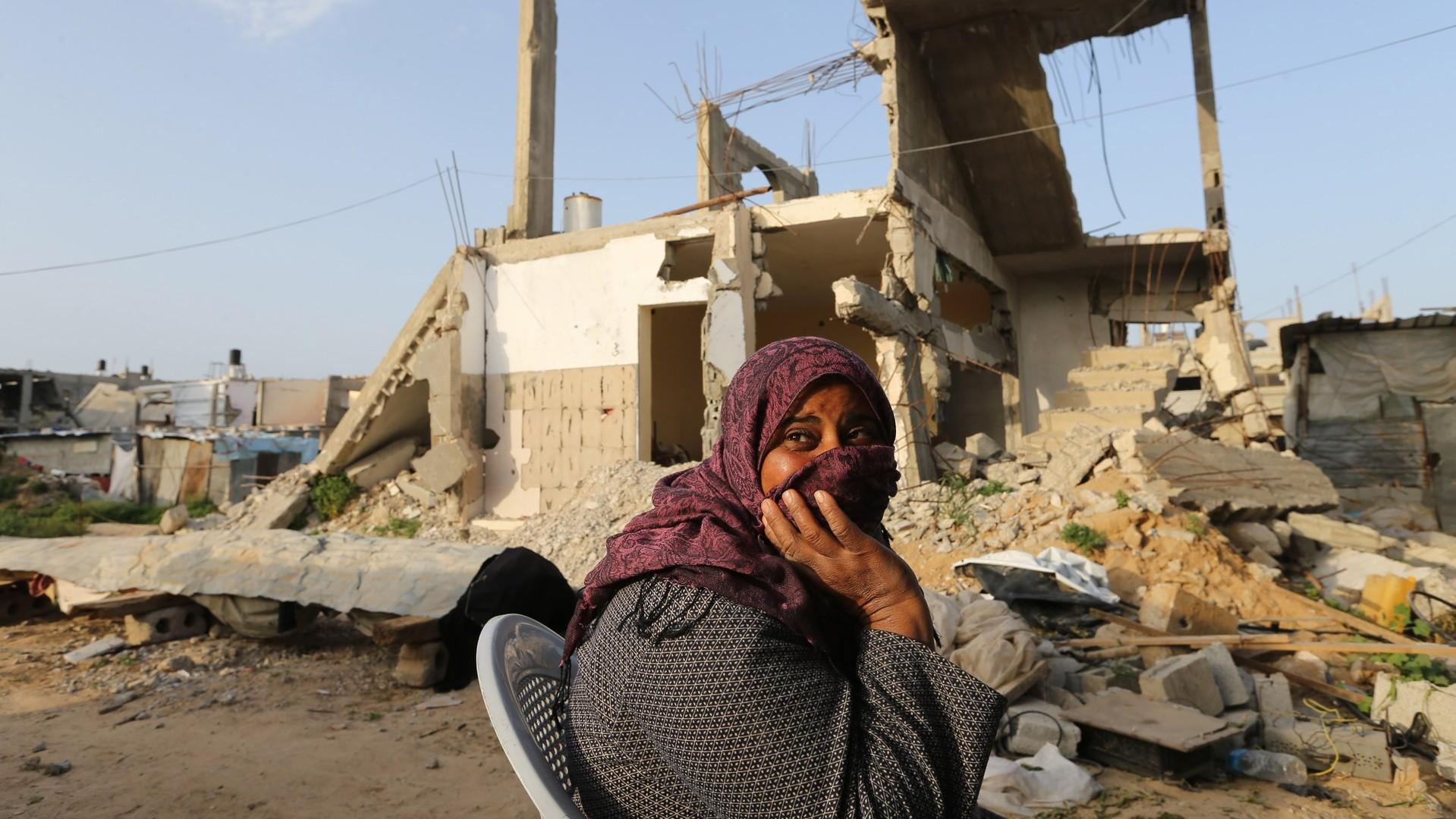 Une femme palestienne près de sa maison détruite
