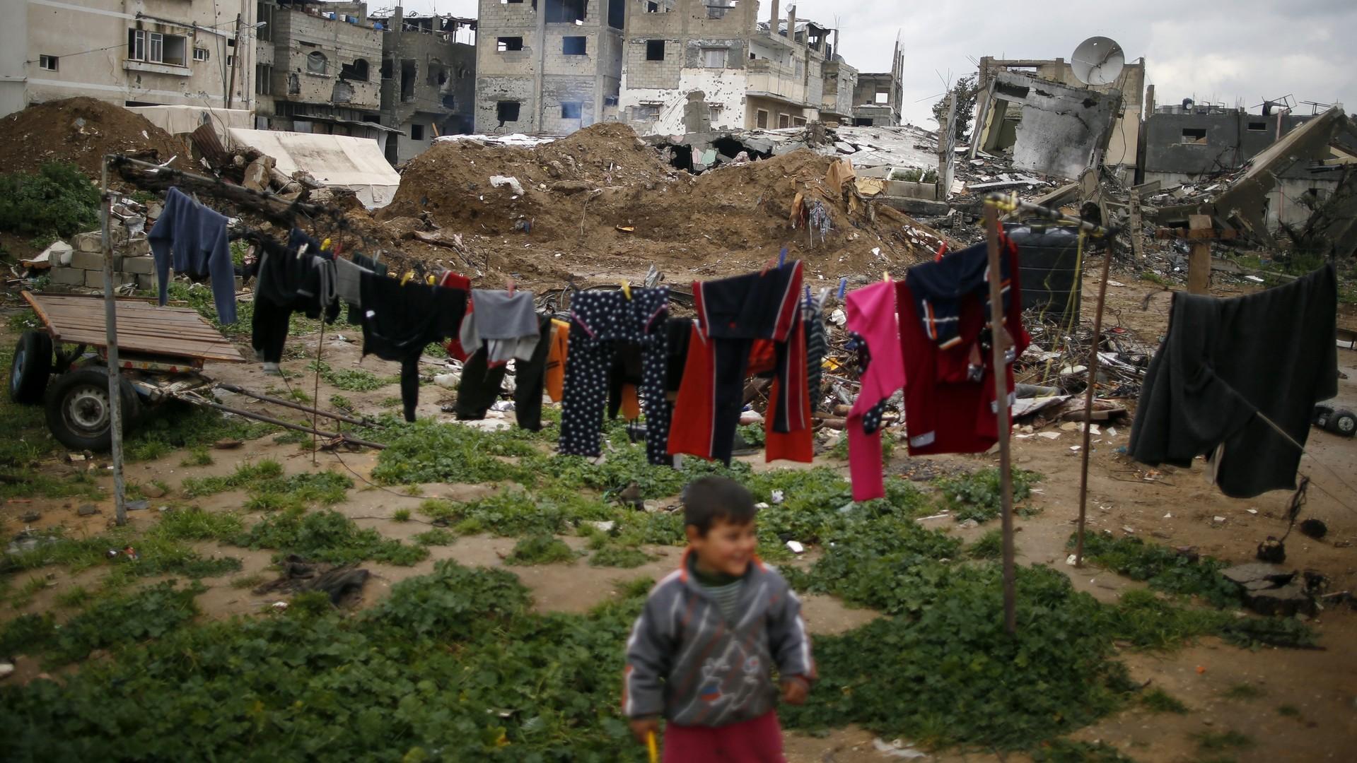 Un garçon palestinien joue près de sa maison détruite