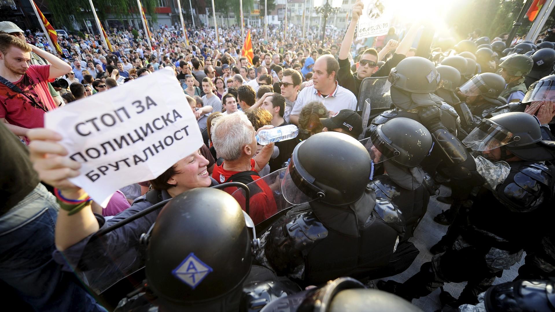 """""""Halte aux violences policières"""", lit-on sur la pancarte d'une jeune manifestante à Skopje"""