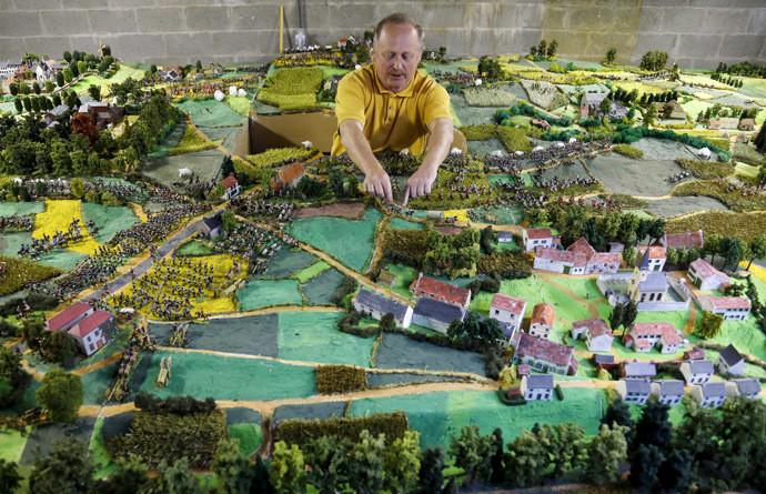 Willy Smout déplace des figurines sur la maquette représentant la bataille du 18 juin 1815