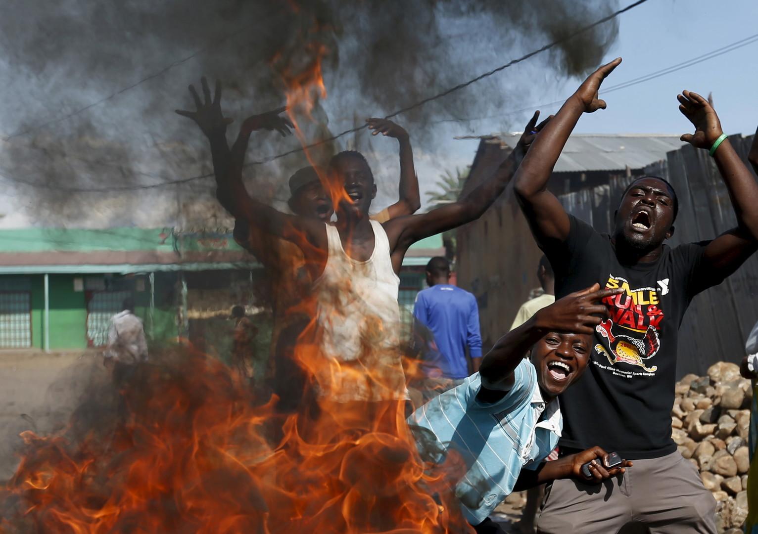 Des protestataires scandent des slogans devant une barricade à Bujumbura