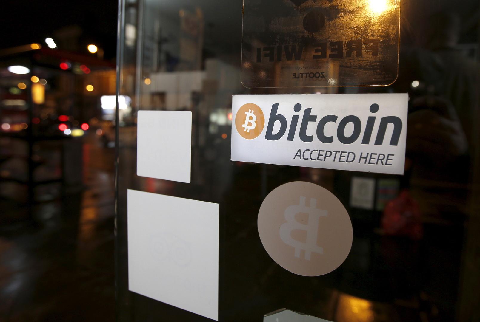 Un signe à l'entrée d'un magasin qui dit «Les bitcoins sont acceptés ici»
