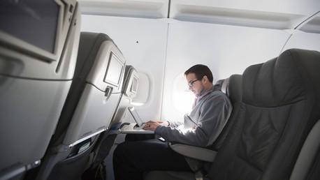 Un homme utilise son ordinateur portable en vol