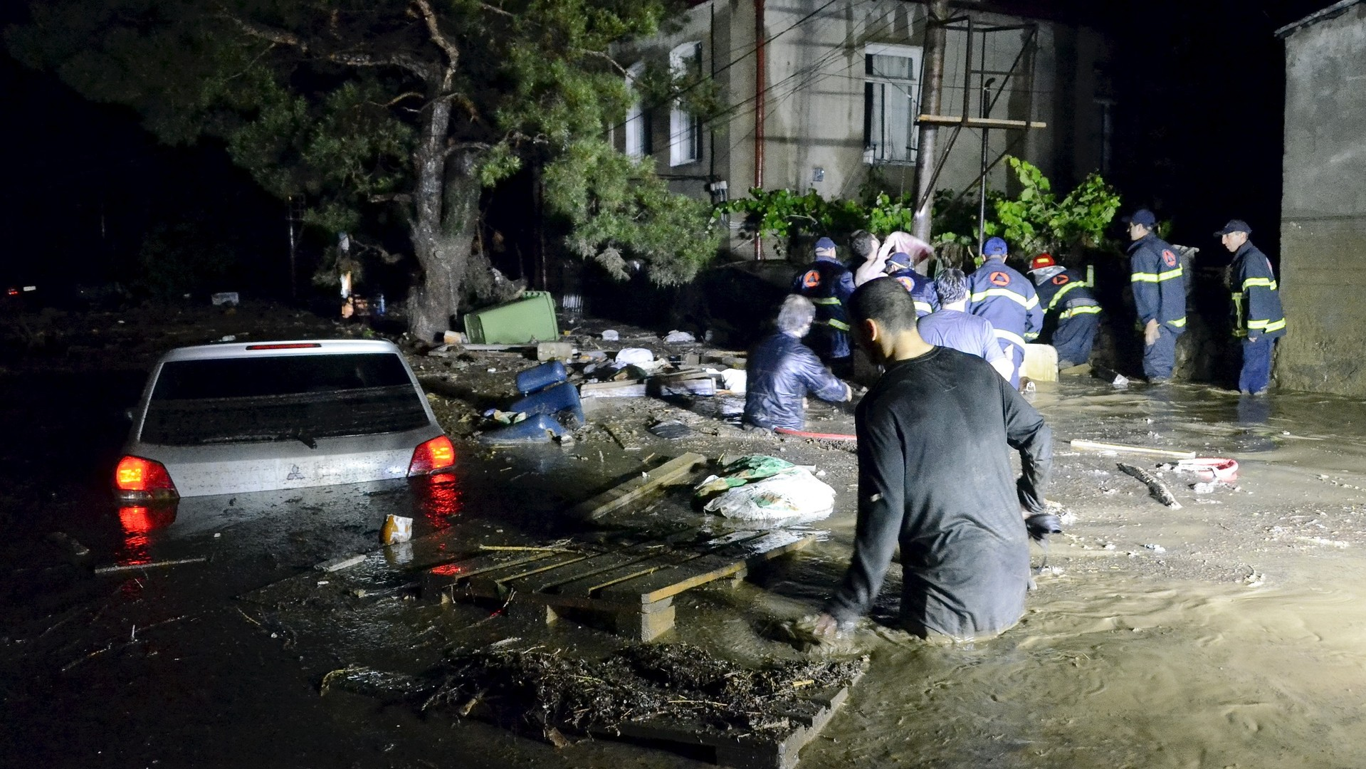 Des habitants et des sauveteurs pataugent dans une rue inondée de Tbilissi