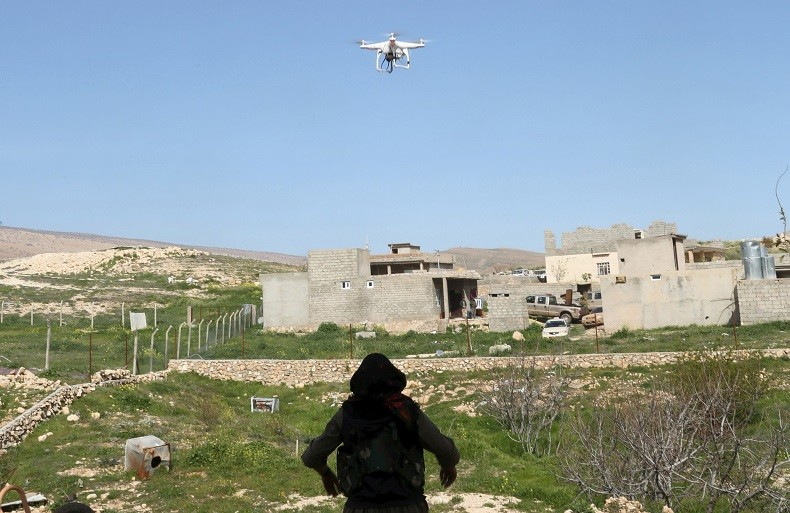 Une femme kurde regarde un drone américain analyser les positions de Daesh