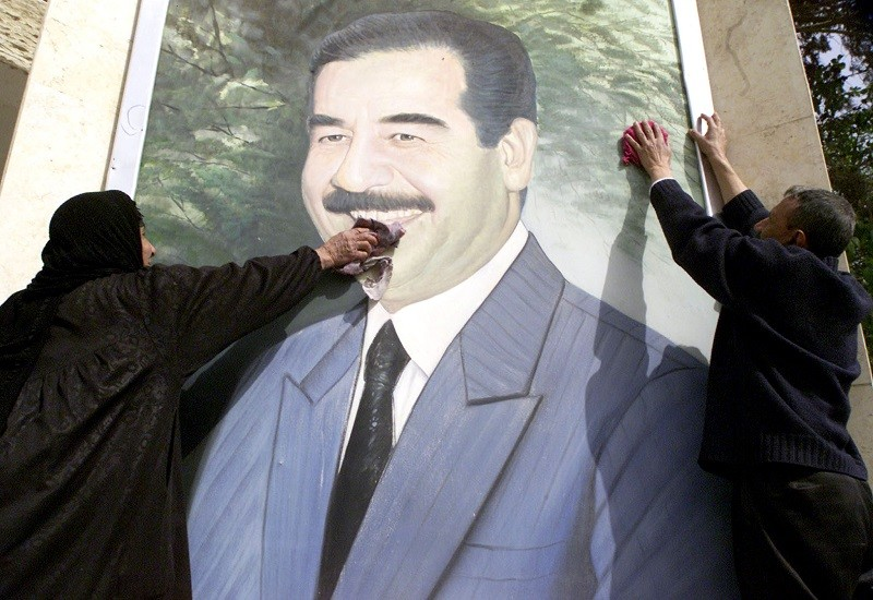 Un portrait de Saddam Hussein poli par des citoyens irakiens