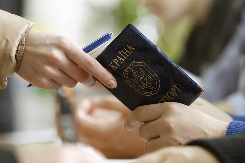 Une femme tend son passeport ukrainien dans un bureau des services de l'immigration russes