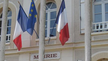 Le drapeau européen entouré de deux drapeaux français sur le fronton d'une mairie