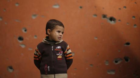 Enfant palestinien se tenant devant un batiment endommagé à Gaza