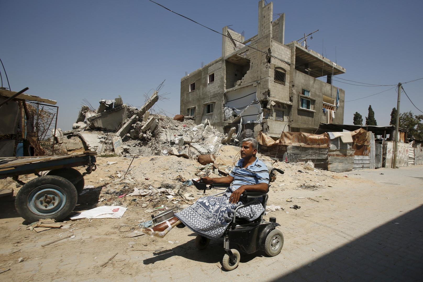 Ali Wahdan pousse son fauteuil roulant dans la rue en face de son ancienne maison