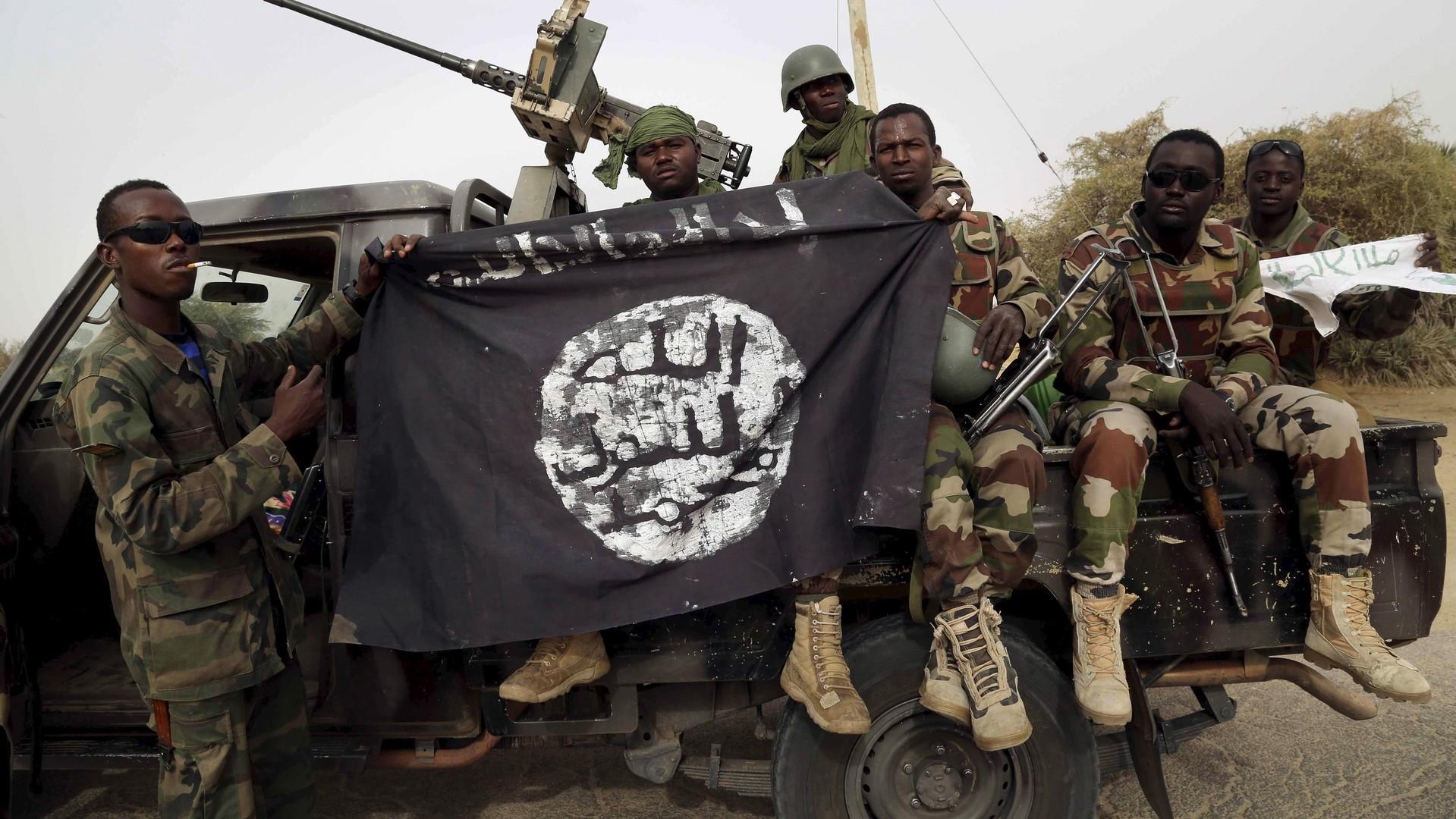 Des soldats nigérians tiennent un drapeau de Boko Haram qu'ils ont capturé
