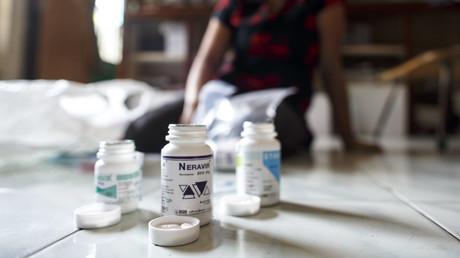 Une femme montre ses médicaments antirétroviraux