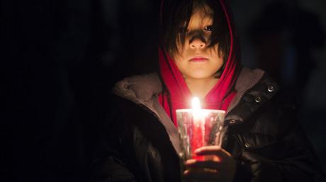 Petite fille tenant une bougie lors d'une manifestation pour les droits des peuples autochtones