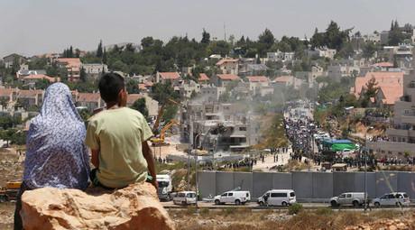 Des Palestiniens regardent les bulldozers israéliens dans la colonie juive de Cisjordanie de Beit El, près de Ramallah le 29 Juillet 2015.