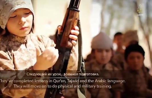 Un enfant apprend à manier la kalachnikov dans un camp d'entraînement de Daesh.