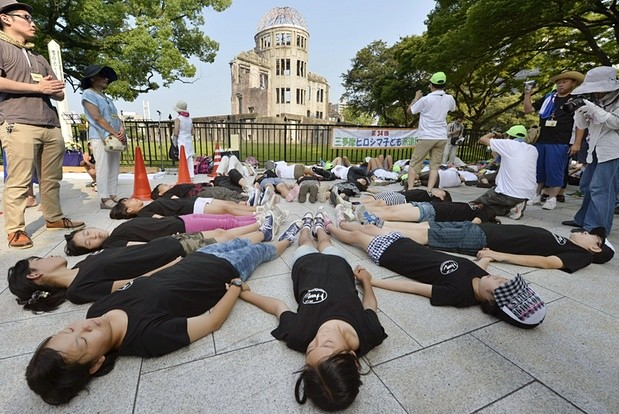 Un groupe d'enfants allongés à terre formant une chaîne humaine représentant les victimes d'Hiroshima.
