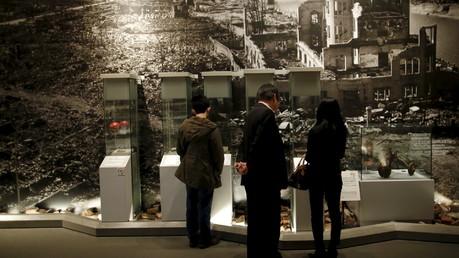 Des visiteurs devant une image avec Hiroshima après les bombardements en 1945