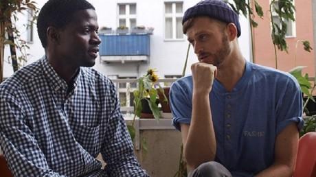 Jonas Kakoschke (à droite) et Bakary Conan discutent dans leur appartement partagé de Berlin