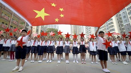 Des écoliers chinois posent avec le drapeau national