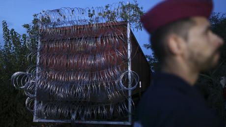 Un train entouré de barbelé sert de mur à la frontière entre la Hongrie et la Serbie.