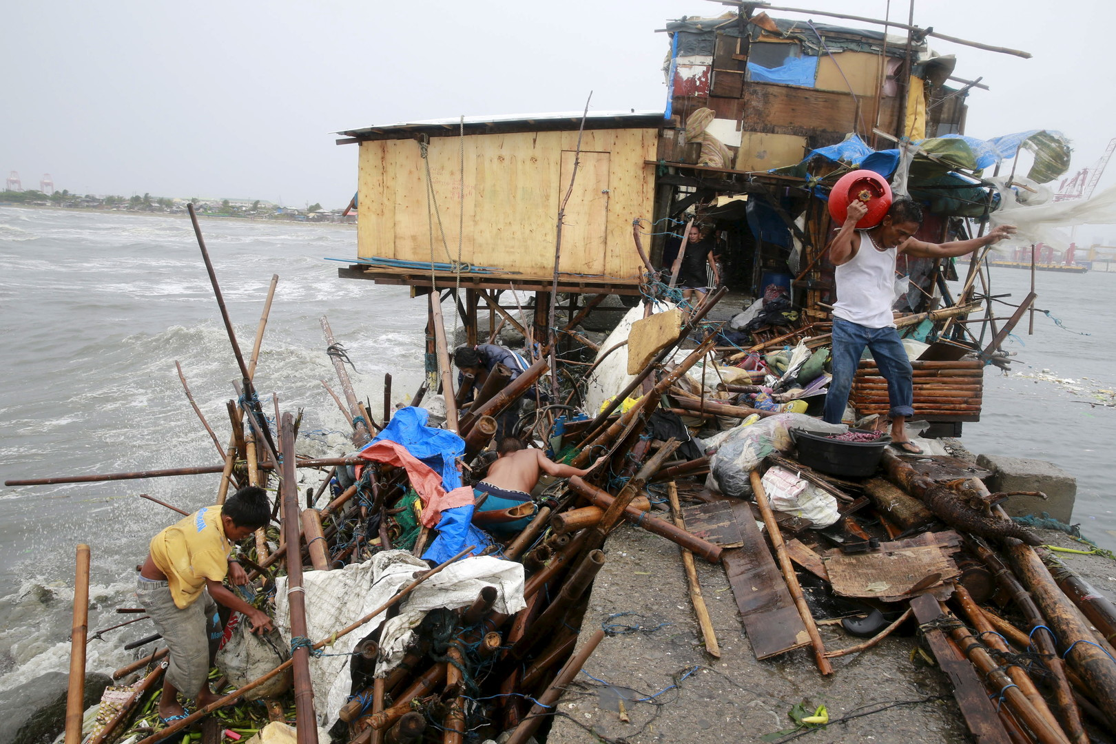 Une famille cherche le long de la côte de la baie de Manille des biens récupérables après la destruction de leur maison