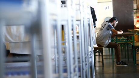 Un réfugié remplit des papiers adminstratifs dans un camp en Allemagne