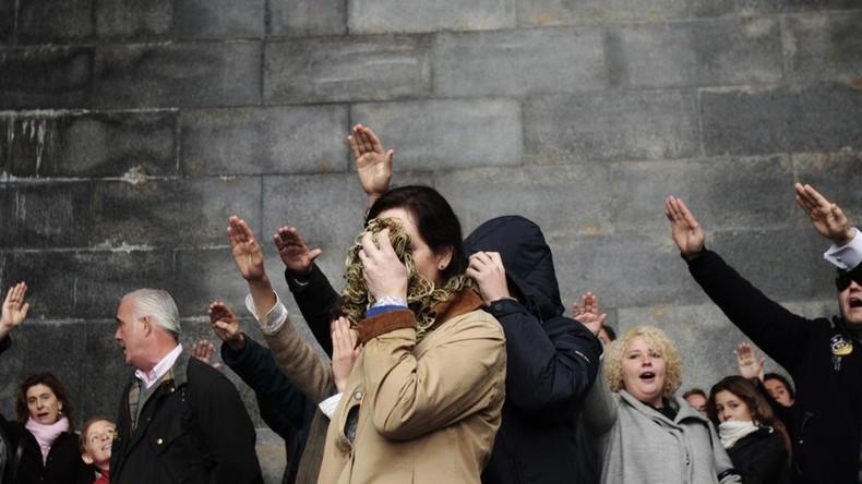 Une femme se cache le visage alors qu'elle effectue un salut fasciste avec d'autres personnes, après avoir assisté à une messe, près de la basilique de Valle de los Caidos, près de Madrid, en novembre 2011.
