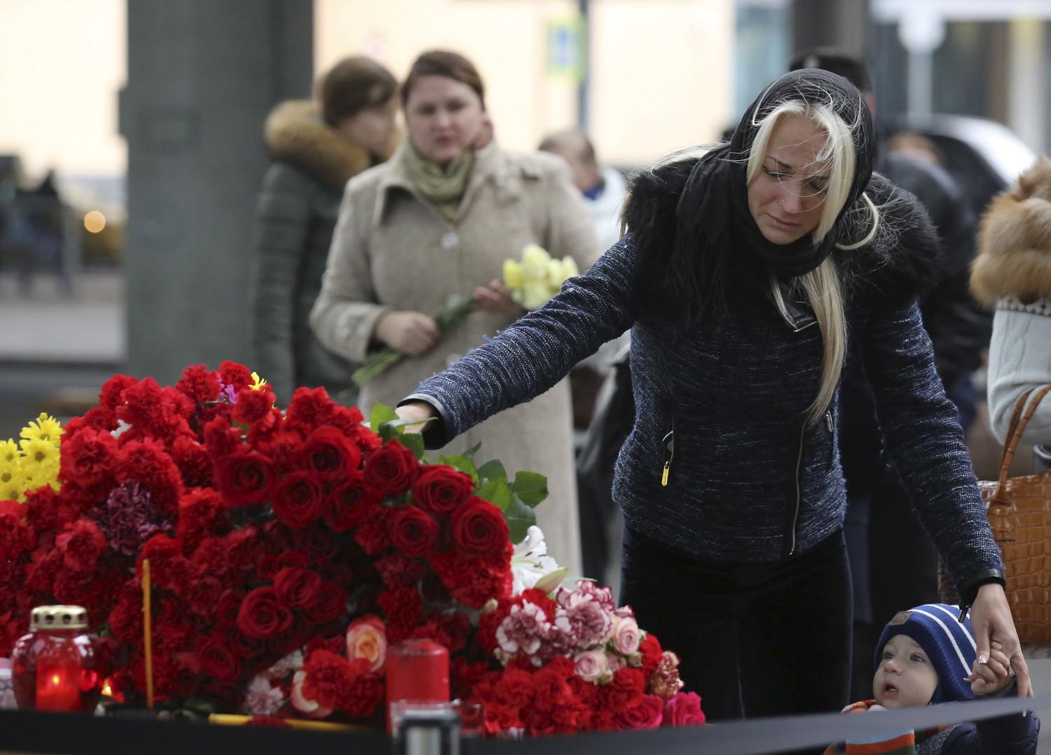 Une femme dépose une gerbe de fleurs près de l'aéroport de Poulkovo à Saint-Pétersbourg, en mémoire des victimes du crash