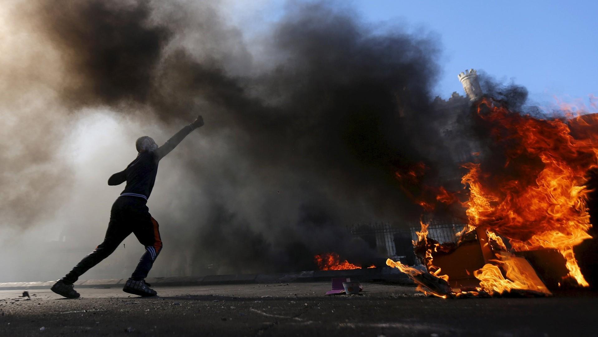 Un manifestant palestinien lance des pierres sur les troupes israéliennes.