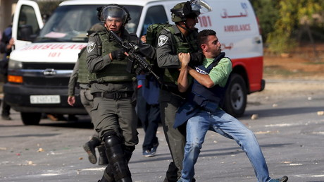 Deux gardes-frontières israéliens maîtrisent sans ménagement un journaliste palestinien lors d'affrontements près de Ramallah