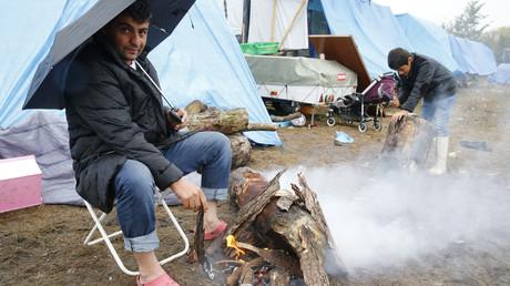 Un migrant fait un feu dans le campement de Calais