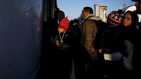 Des réfugiés montent dans un bus après avoir atteint le port du Pirée par ferry depuis l'île de Lesbos
