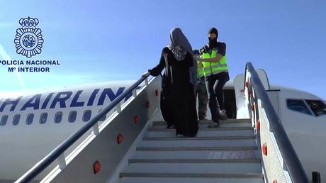La femme est escortée par les forces de sécurité hors de l'avion.
