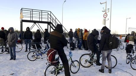 Des réfugiés à vélo à proximité du checkpoint de la frontière russo-norvégienne