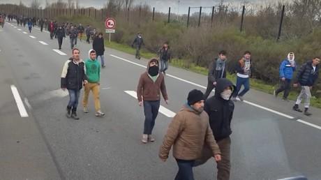 Des migrants sur l'autoroute menant au port de Calais essaie de grimper dans des camions