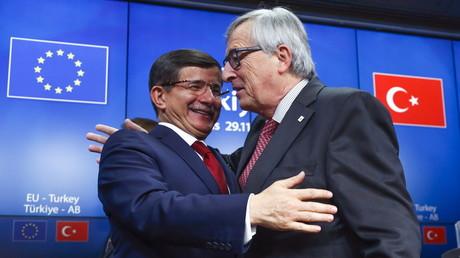 Le premier ministre turc Ahmet Davutoglu embrasse le président de la Commission Européenne Jean Claude Juncker après le sommet UE-Turquie à Bruxelles le 29 novembre 2015.