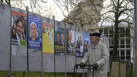 Un homme regarde les affiches de campagne dans la région Nord-Pas-de-Calais-Picardie.