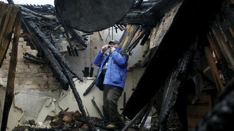 Un observateur de l'OSCE prend une photo d'une maison détruite à Donetsk