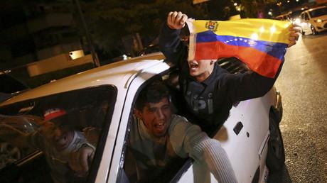 Des partisans de l'opposition vénézuélienne brandissent un drapeau national a Caracas en fêtant la première victoire de l'opposition aux élections parlementaires depuis 16 ans.
