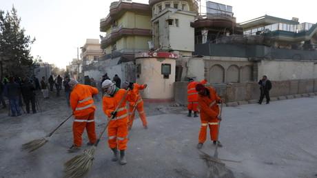 Des agents municipaux nettoient la route après l'attentat à proximité de l'ambassade d'Espagne à Kaboul