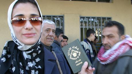 Une femme montre son nouveau passeport irakien devant un bâtiment officiel.