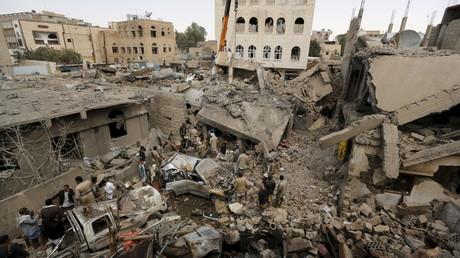 A Sanaa, capitale du Yémen, des gens se rassemblent autour des décombres de maisons détruites.