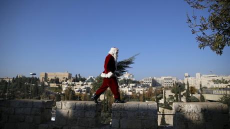Un homme en costume de Père Noël sur le sur de la vielle ville de Jérusalem