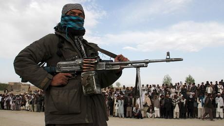 Combattant taliban derrière une foule venue assister en avril 2015 à l'exécution de trois hommes accusées d'avoir tués un couple au moment d'un vol dans la province de Ghazni