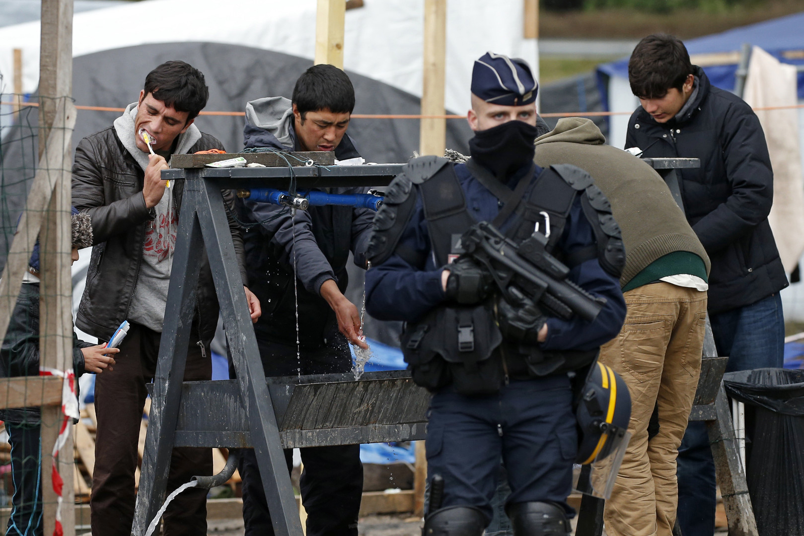 Un policier dans le camp de Calais devant des migrants qui se lavent les dents