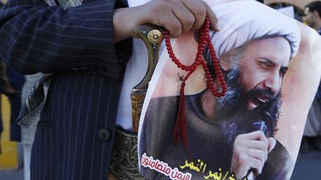 Un homme arborant le portrait du Cheikh Nimr al-Nimr.