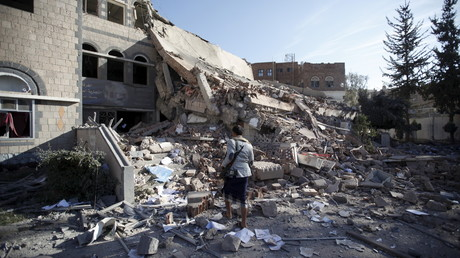 Un militant houthi marche dans les décombres de la chambre de commerce et d'industrie à Sanaa, la capitale yéménite, ce 5 janvier