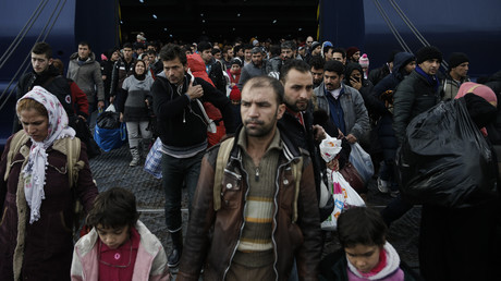 Des réfugiés et des migrants arrivent à bord du ferry Ariadne au port du Pirée à Athènes